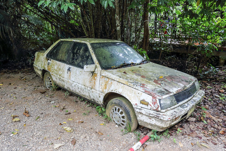 Old rusted car in junk yard photo