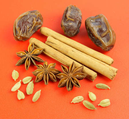 Four spices representing a cosy winter evening baking session. Pods of green Cardamom and fruits of star anise are placed in front of Cinnamon sticks and Medjoul dates on a warm red sheet.  photo