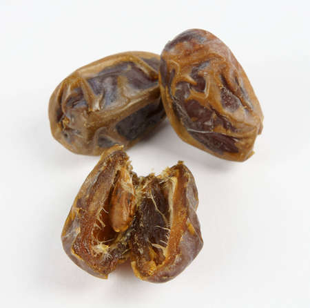 Medjoul date in focus cut up showing the seed in front of two whole fruits; on neutral white background.
