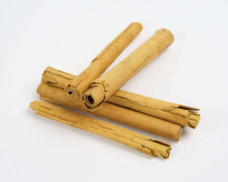 Set of Ceylon Cinnamon (Cinnamomum verum) sticks placed diagonally with one set off in front, and two placed squarely on top of the others; focus on front end of center sticks.