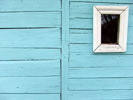 A wooden wall with a small window