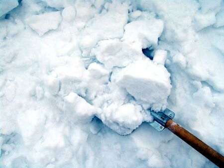 Cleaning snow with a metallic shovel Imagens