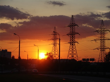 An urbanistic landscape at evening with a highway and power poles Stock Photo