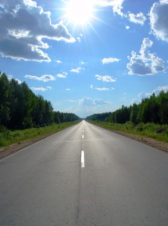 A road continuing to infinity in a forest land and the shining white sun