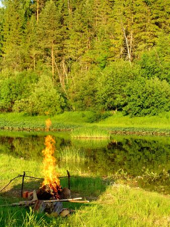 A fire burning on a river shore in the evening