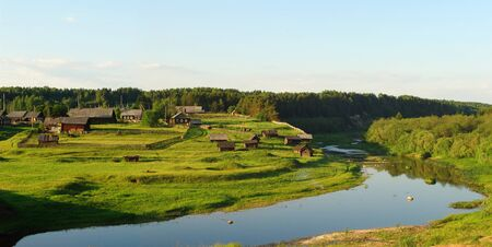 A panoramic view of a northern russian village with a river flowing near Imagens