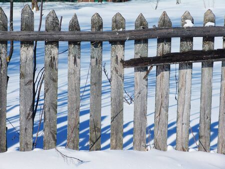 An old woonen fence by a winter day photo