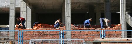 Four workers in a row constructing a part of a building Stock Photo