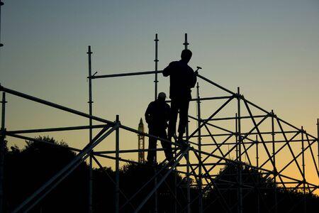 Silhouetten van twee bouwers bouw iets in de avond