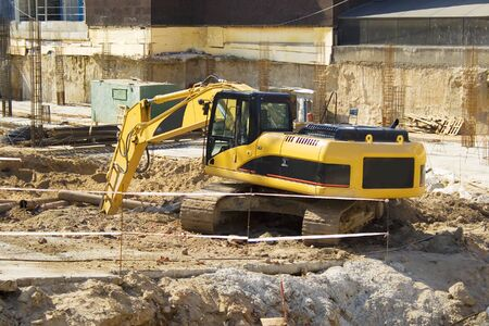 A yellow dredger excavating ground on a construction site