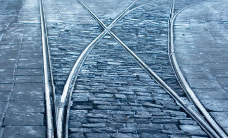 A closeup of a tram rail switch with city pavement