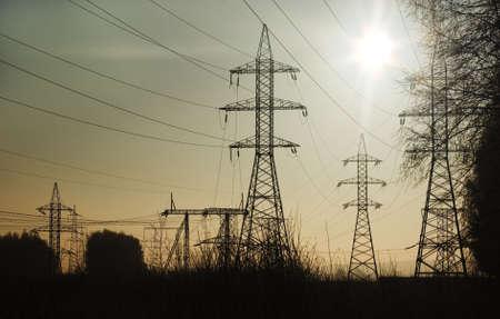 isolator insulator: Power line silhouettes against sun light