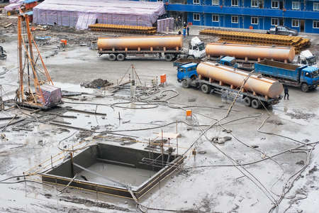 buildup: A construction site on the basement phase with drilling equipment and workers on it Stock Photo
