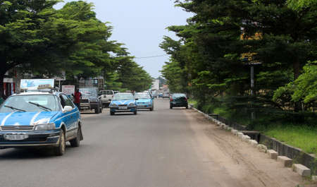 City roads view and colorful painted taxi cars in Pointe-Noire, Congo Republic, february 2015 Stock Photo - 81330805