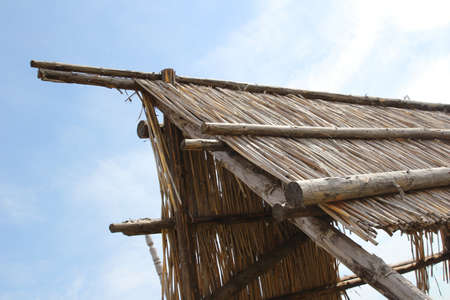 A traditional straw barn roof over a blue sky Stock Photo