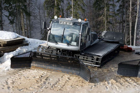 View of a small shining snow tracktor to level snow and help sportsmen
