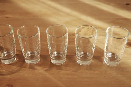 A number of small shot glasses on a wooden table