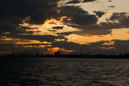 thessaloniki: A beautiful sunset at Thessaloniki. In the background we see the port and the derricks