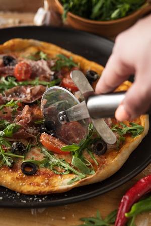 Traditional pizza with prosciutto and arugula Stock Photo