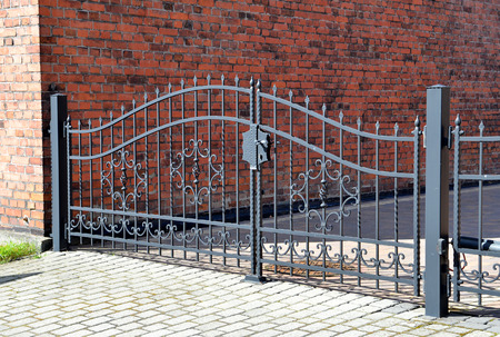 iron fence: Forged iron gate outdoor. Black grey fence. Stock Photo