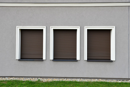 Outdoor three window blinds closed on grey wall