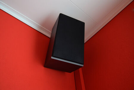 public address: Musical speaker column on a red wall ceiling. Stock Photo