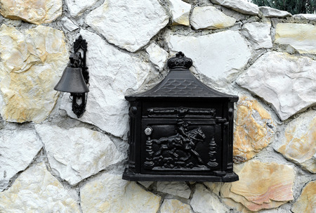 Classic mailbox and Vintage doorbell on a house stone wall photo
