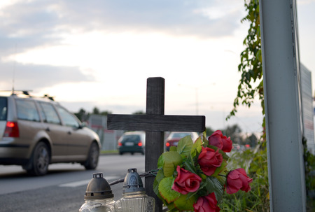 all souls day: View of roadside memorial with cross, candles and flowers. All Souls Day