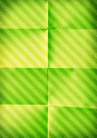diagonals: Folded diagonal striped paper. Green color background. Stock Photo