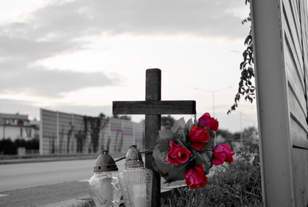 View of roadside memorial with cross, candles and flowers. All Souls Day