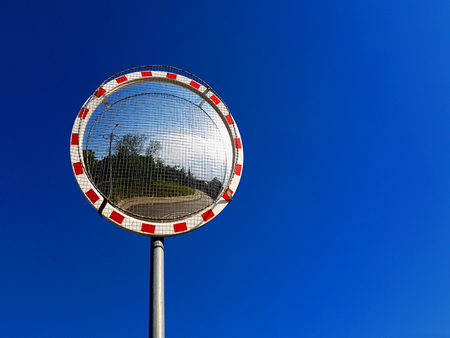 Road convex mirror on blue sky