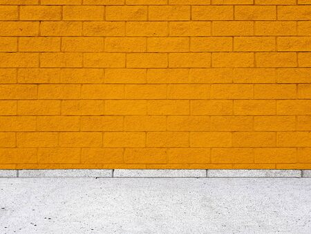 Brick wall with regular shapes and a rough surface. Empty orange background facade building with sidewalk.