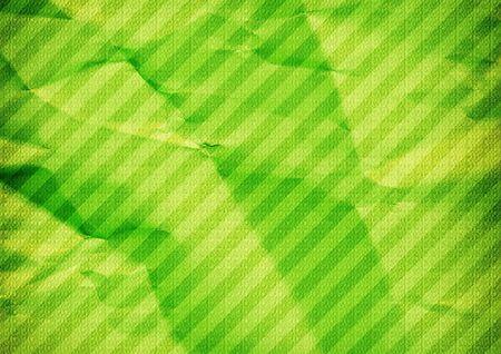 Green color background. Folded diagonal striped paper. Foto de archivo