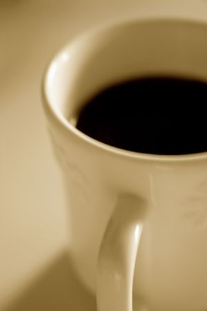 emphasize: Toned photo of a morning cup of coffee: shallow depth of field to emphasize mood