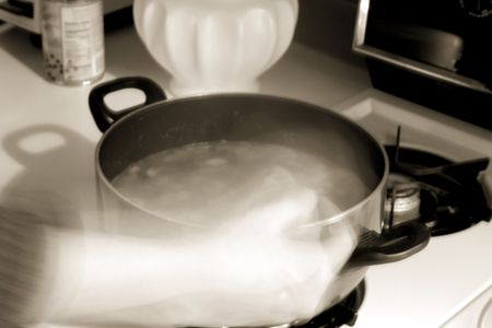 Photo of a woman stirring a pot of soup in the kitchen Stock Photo