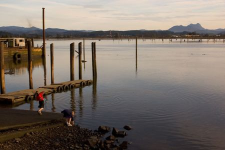 Photo Girls throwing rocks at Youngs Bay in Astoria, Oregon at sunset photo