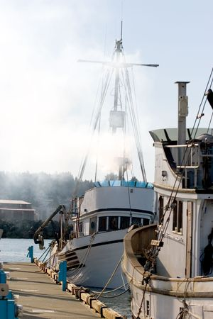 polluting: Photo of a fishing boat polluting the air. Stock Photo