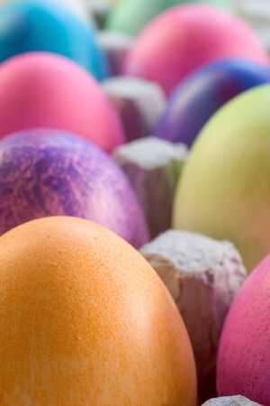 A Dozen colored Easter eggs in a carton on a white background photo