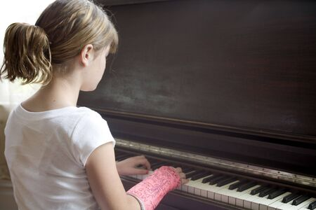 Photo of Maggie in a pink cast playing the piano. Stock Photo