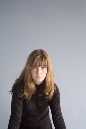 ennui: Photo of a girl against a blue wall.