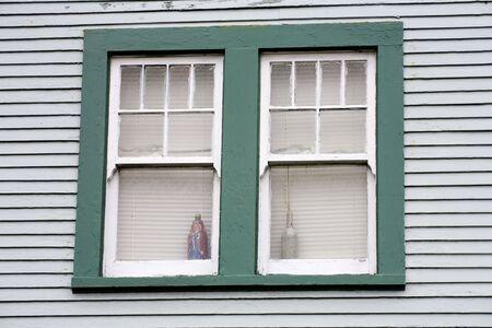 unattractive: Photo of an unattractive green window and blue siding.