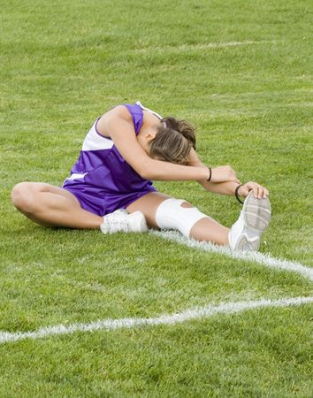 Photo of a girl cross country runner stretching in a purple uniform. Stock Photo