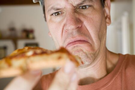 Photo of a man eating pepperoni pizza.