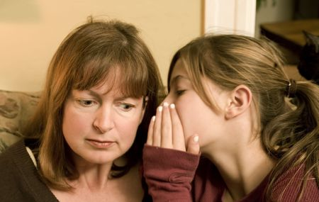 Photo of an attractive woman listening to her daughters secret. Stock Photo