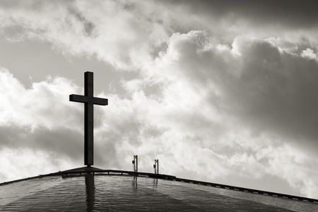 Photo of a cross against blue sky with clouds. Stock Photo