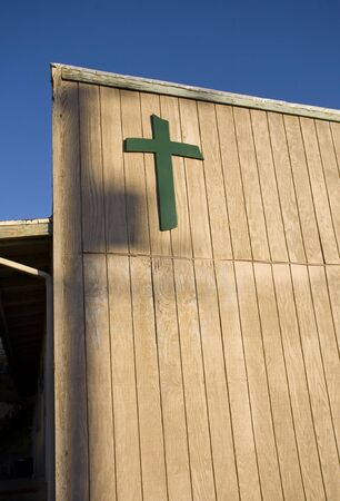 unattractive: Photo of a cross on an unattractive builidin and blue sky. Stock Photo