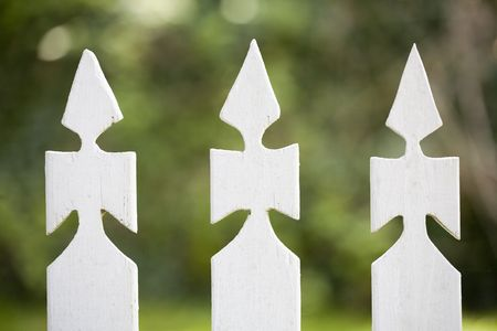 picket green: Photo of an antique picket fence with a green background. Stock Photo