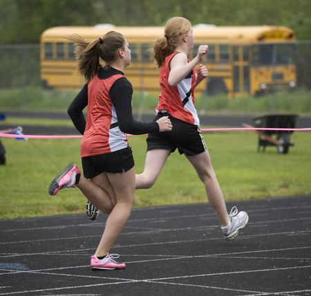 Two sprinters in orange and black crossing the finish line.