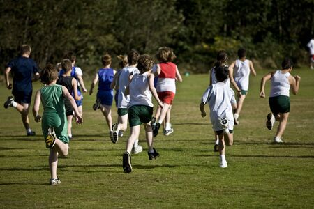 Cross country runners take off in a pack from the starting line.