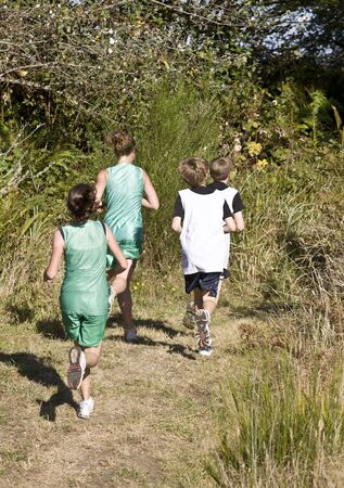 Cross country runners on a wooded trail: both male and female runners are shown.